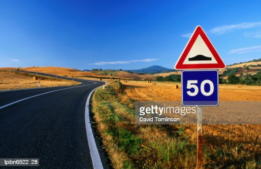 Speed sign on winding road near San Quirico d'Orica., Tuscany, Italy, Europe