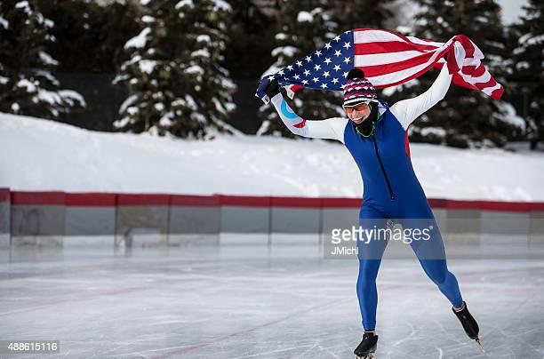 Pattinaggio di velocità portare la bandiera americana durante il giro d'onore.