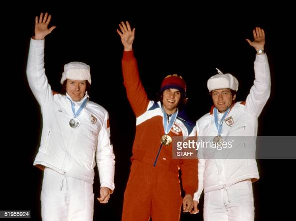 US speed skater Eric Heiden flanked by Norwegians Kai Arne Stenshjemmet and Terje Andersen smiles as he waves to the crowd during the medals ceremony...