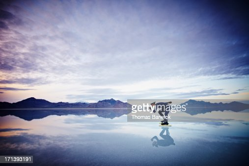 Speed skater skating on calm lake at sunset : Stock Photo