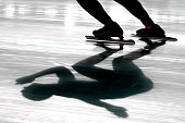 The shadow of an ice speed skater is seen on an open air track.