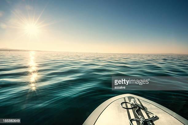 speedboat on lake driving against sun