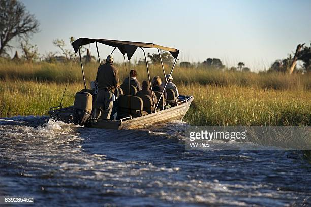 A speedboat sails the Okavango Delta on an organized camp from Eagle Island Camp by Orient Expressoutside the Moremi Game Reserve in Botswana safari...