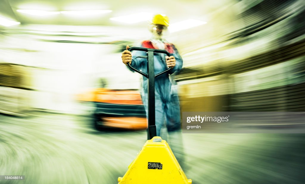 Speeding forklift in the busy warehouse : Stock Photo