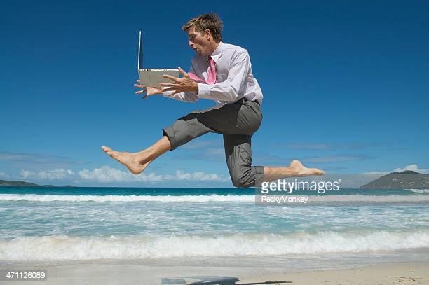 Speedy Homme d'affaires de sauter sur la plage tropicale avec ordinateur portable
