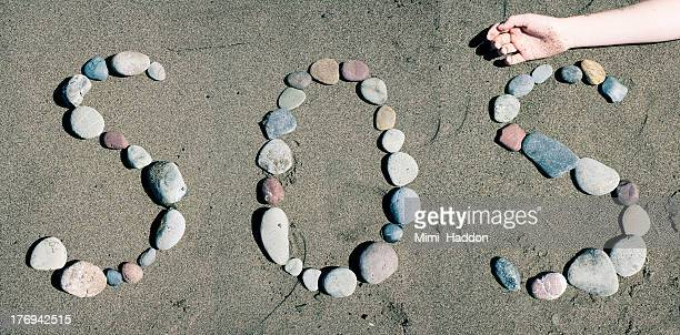 S.O.S. Spelled With Rocks in Sand