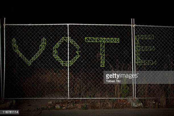 VOTE spelt on a chain link fence