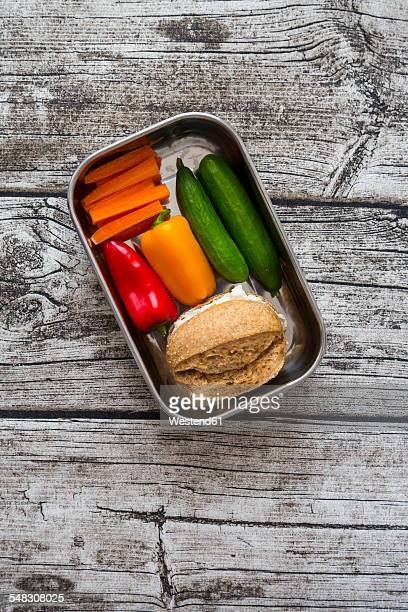 Spelt roll with cream cheese and carrots, bell peppers and cucumbers in metal box