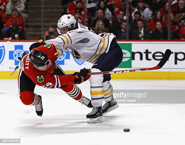 Spencer Abbott of the Chicago Blackhawks tries to get off a shot as he's knocked to the ice by Rasmus Ristolainen of the Buffalo Sabres at the United...