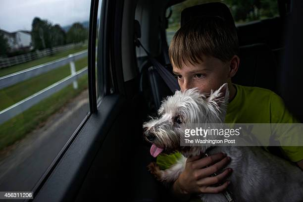 Spencer Bergman holds his new dog Coconut as the family drives by the scene of the August robbery of Spencer's lemonade stand in Round Hill Virginia...