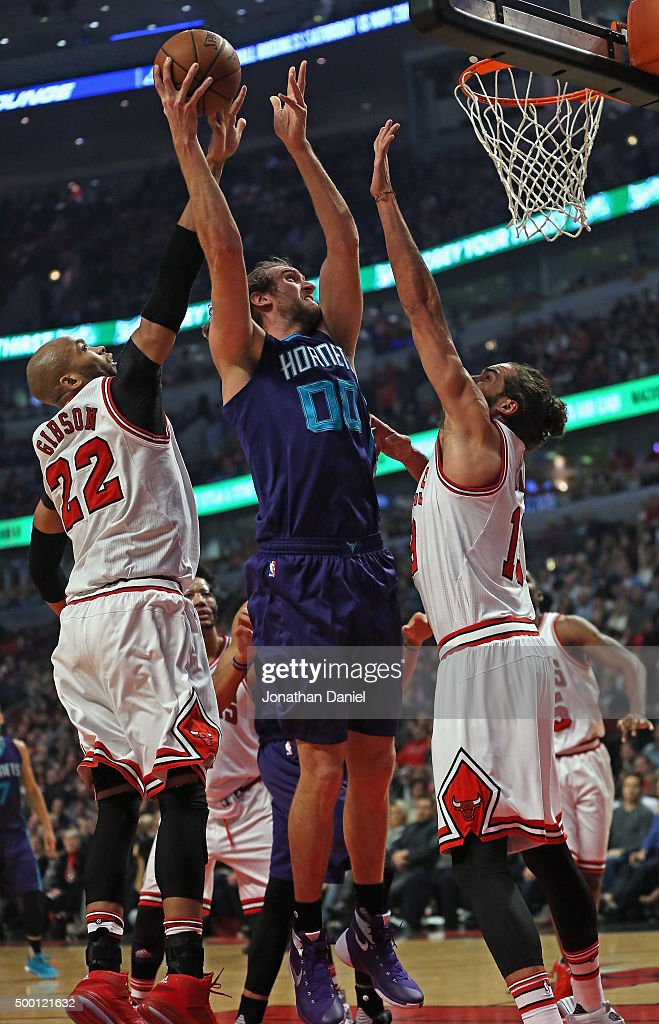 Spencer Hawes #00 of the Charlotte Hornets gets off a shot between Taj Gibson #22 and Joakim Noah #13 of the Chicago Bulls at the United Center on December 5, 2015 in Chicago, Illinois. Note to User: User expressly acknowledges and agrees that, by downloading and or using the photograph, User is consenting to the terms and conditions of the Getty Images License Agreement.