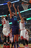 Spencer Hawes of the Charlotte Hornets gets off a shot between Taj Gibson and Joakim Noah of the Chicago Bulls at the United Center on December 5...