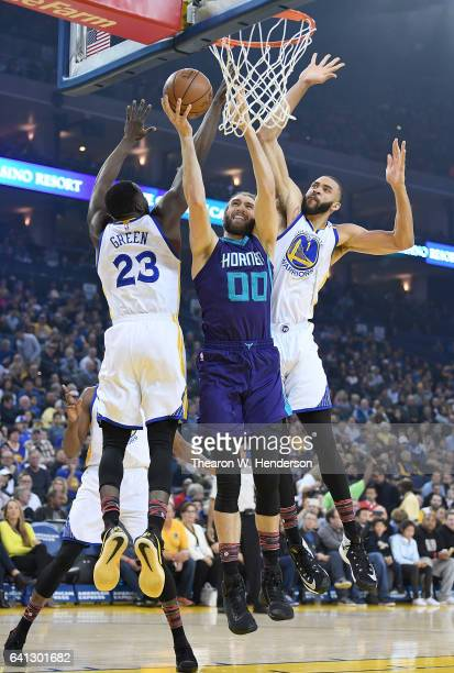 Spencer Hawes of the Charlotte Hornets goes up to shoot over Draymond Green and JaVale McGee of the Golden State Warriors during an NBA basketball...