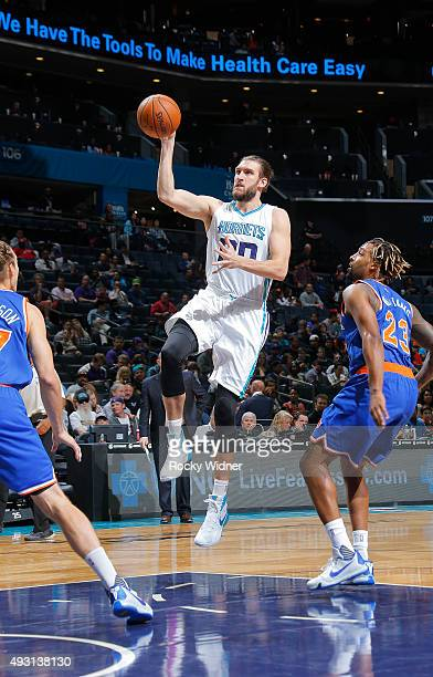 Spencer Hawes of the Charlotte Hornets shoots against Derrick Williams of the New York Knicks on October 17 2015 at Time Warner Cable Arena in...