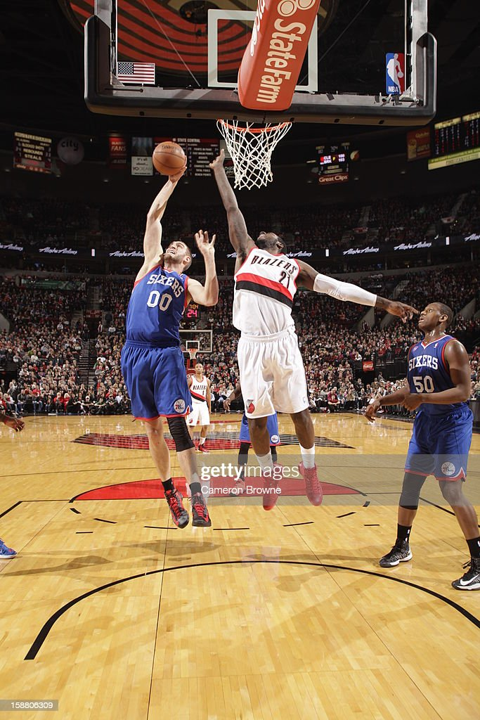 Spencer Hawes #00 of the Philadelphia 76ers and J.J. Hickson #21 of the Portland Trail Blazers battle for the ball control during the game between the Philadelphia 76ers and the Portland Trail Blazers on December 29, 2012 at the Rose Garden Arena in Portland, Oregon.