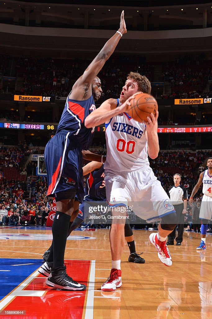 <a gi-track='captionPersonalityLinkClicked' href=/galleries/search?phrase=Spencer+Hawes&family=editorial&specificpeople=3848319 ng-click='$event.stopPropagation()'>Spencer Hawes</a> #00 of the Philadelphia 76ers drives against <a gi-track='captionPersonalityLinkClicked' href=/galleries/search?phrase=Anthony+Tolliver&family=editorial&specificpeople=4195496 ng-click='$event.stopPropagation()'>Anthony Tolliver</a> #4 of the Atlanta Hawks during the game at the Wells Fargo Center on December 21, 2012 in Philadelphia, Pennsylvania.
