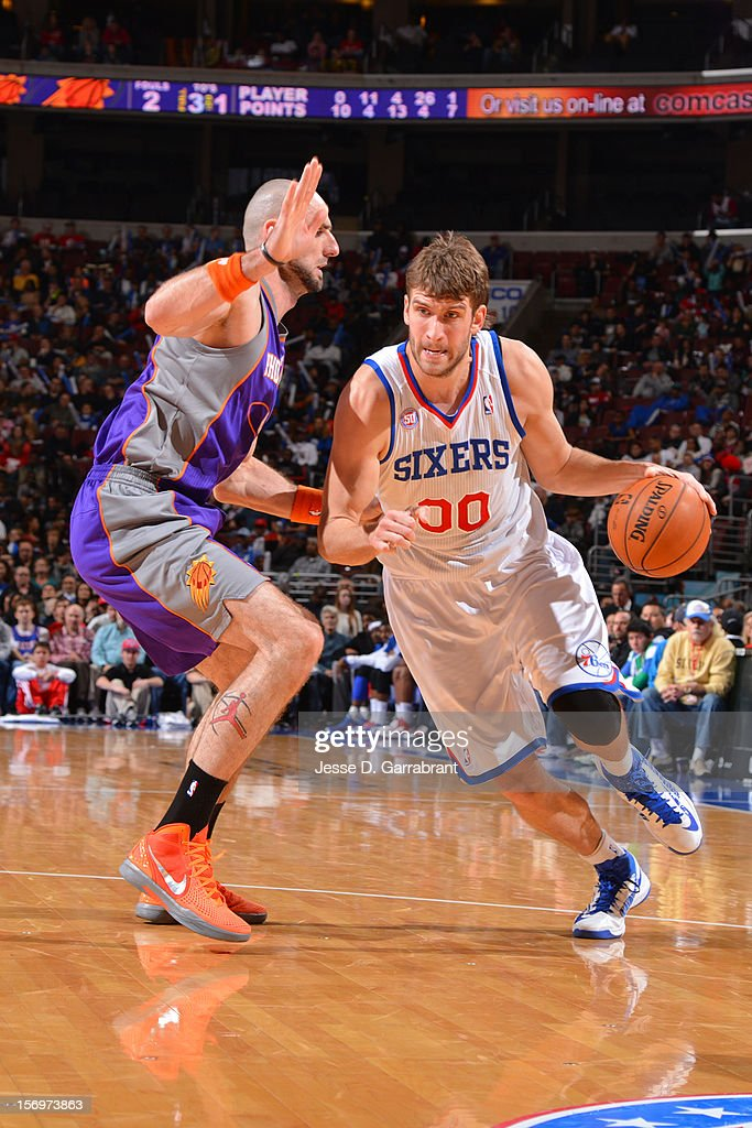 Spencer Hawes #00 of the Philadelphia 76ers drives to the basket against Marcin Gortat #4 of the Phoenix Suns at the Wells Fargo Center on November 25, 2012 in Philadelphia, Pennsylvania.