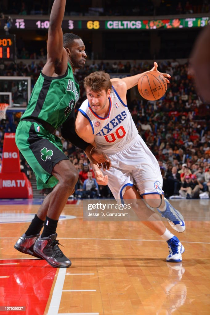 Spencer Hawes #00 of the Philadelphia 76ers drives to the basket against Jeff Green #8 of the Boston Celtics at the Wells Fargo Center on December 7, 2012 in Philadelphia, Pennsylvania.