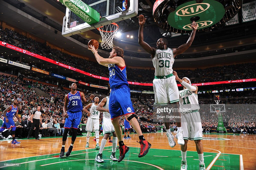 Spencer Hawes #00 of the Philadelphia 76ers rises for a layup against Brandon Bass #30 of the Boston Celtics on December 8, 2012 at the TD Garden in Boston, Massachusetts.