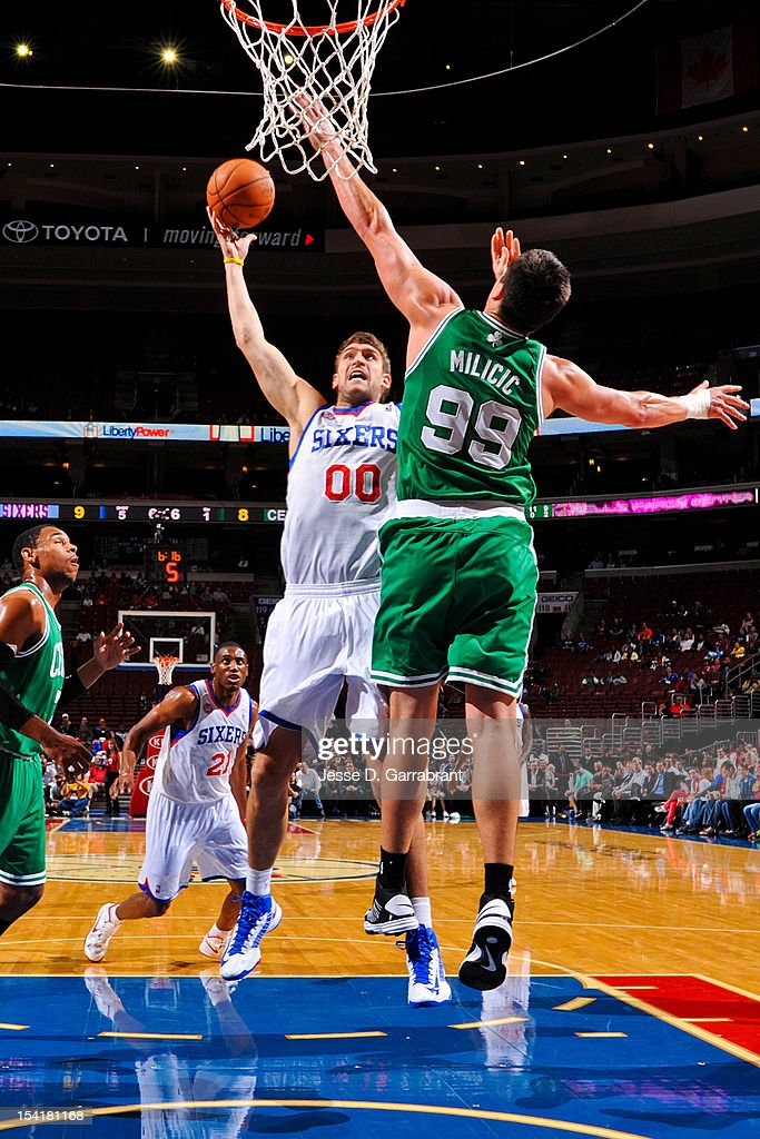 <a gi-track='captionPersonalityLinkClicked' href=/galleries/search?phrase=Spencer+Hawes&family=editorial&specificpeople=3848319 ng-click='$event.stopPropagation()'>Spencer Hawes</a> #00 of the Philadelphia 76ers shoots against <a gi-track='captionPersonalityLinkClicked' href=/galleries/search?phrase=Darko+Milicic&family=editorial&specificpeople=204586 ng-click='$event.stopPropagation()'>Darko Milicic</a> #99 of the Boston Celtics during a pre-season game at the Wells Fargo Center on October 15, 2012 in Philadelphia, Pennsylvania.
