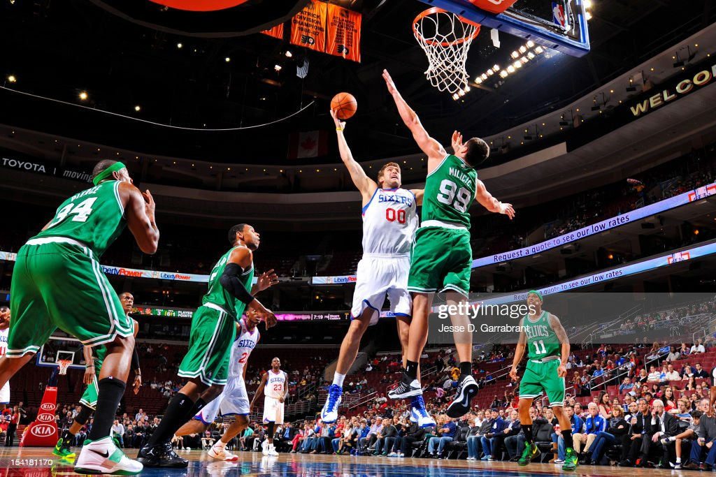 Spencer Hawes #00 of the Philadelphia 76ers shoots against Darko Milicic #99 of the Boston Celtics during a pre-season game at the Wells Fargo Center on October 15, 2012 in Philadelphia, Pennsylvania.
