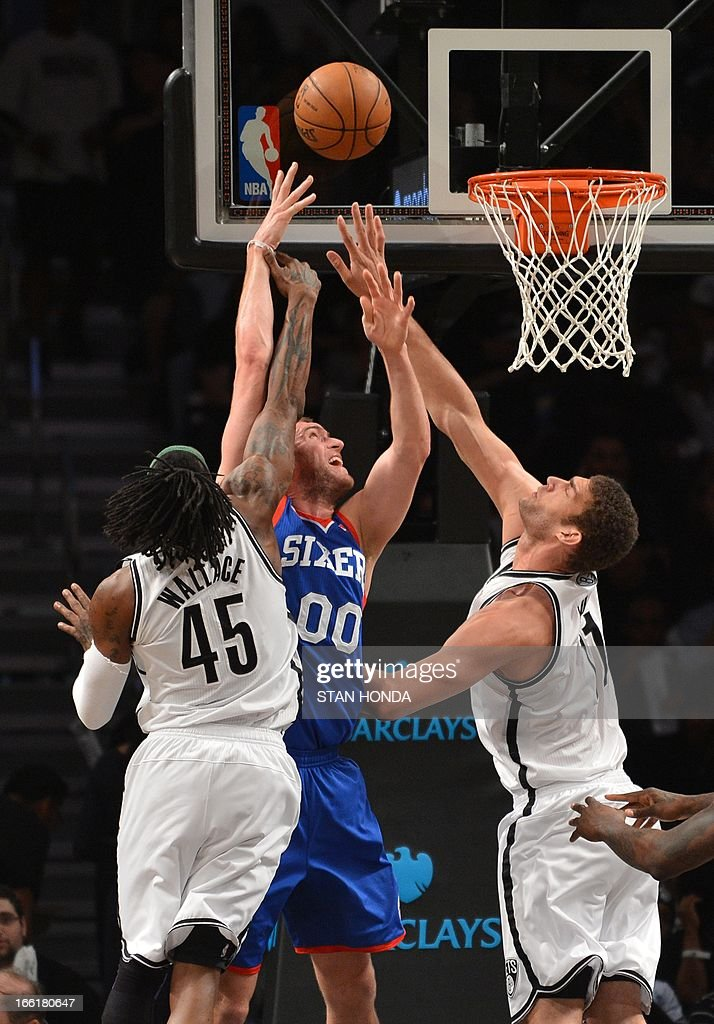 Spencer Hawes (C) of the Philadelphia 76ers shoots against Gerald Wallace (L) and Brook Lopez (R) of the Brooklyn Nets at the Barclays Center April 9, 2013 in the Brooklyn borough of New York. The Nets won, 104-83. AFP PHOTO/Stan HONDA