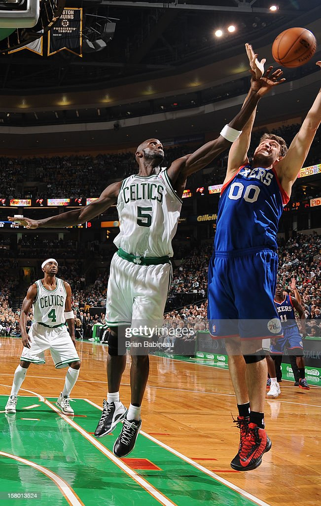 Spencer Hawes #00 of the Philadelphia 76ers takes down a rebound against Kevin Garnett #5 of the Boston Celtics on December 8, 2012 at the TD Garden in Boston, Massachusetts.