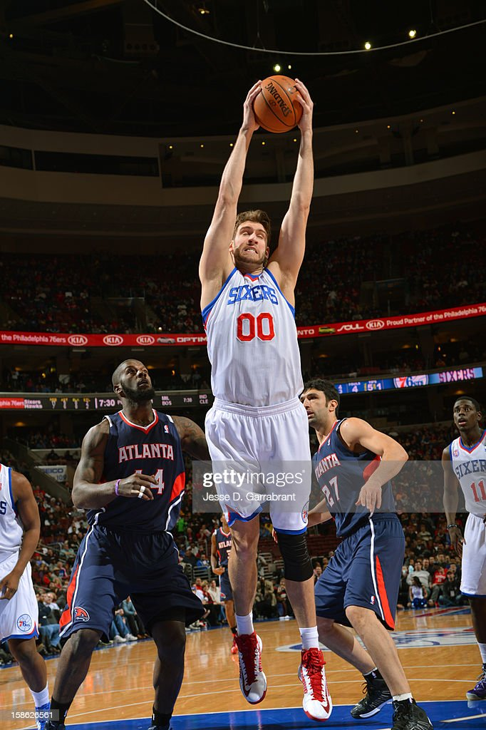 Spencer Hawes #00 of the Philadelphia 76ers takes down a rebound against Ivan Johnson #44 of the Atlanta Hawks at the Wells Fargo Center on December 21, 2012 in Philadelphia, Pennsylvania.