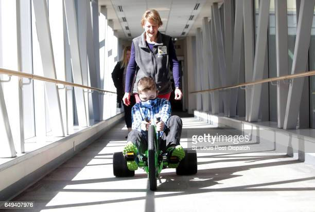 Spencer Kolman of Chicago takes a spin on a Green Machine with his physical therapist Carol Hyde to work on his cardiovascular endurance on Monday...