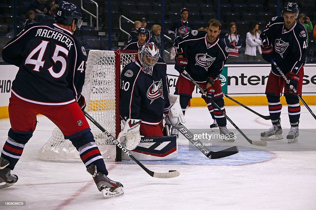 Spencer Machacek #45 of the Columbus Blue Jackets shoots a puck on Mike McKenna #30 of the Columbus Blue Jackets during warmups prior to the start of the game against the the Buffalo Sabres on September, 2013 at Nationwide Arena in Columbus, Ohio.