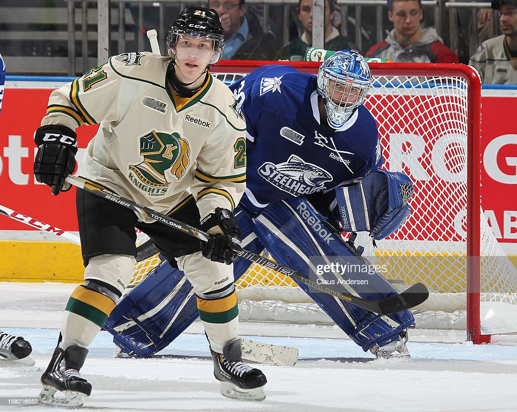 Spencer Martin #30 of the Mississauga Steelheads looks past a screening Tyler Ferry #21 of the London Knights in an OHL game on December 9, 2012 at the Budweiser Gardens in London, Ontario, Canada. The Knights defeated the Steelheads 5-2 and tied their franchise record of 18 straight wins.