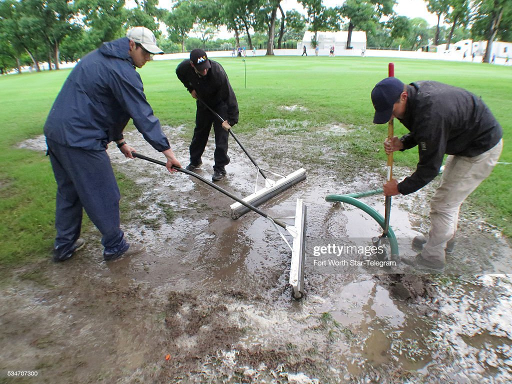 Spencer McCasin, left, Nathan Filloon and Sean Kleinfelter of the Colonial Country Club grounds crew squeegee water from the third fairway into a drain during a morning rain delay on May 27, 2016 at the Dean & DeLuca Invitational in Fort Worth, Texas.