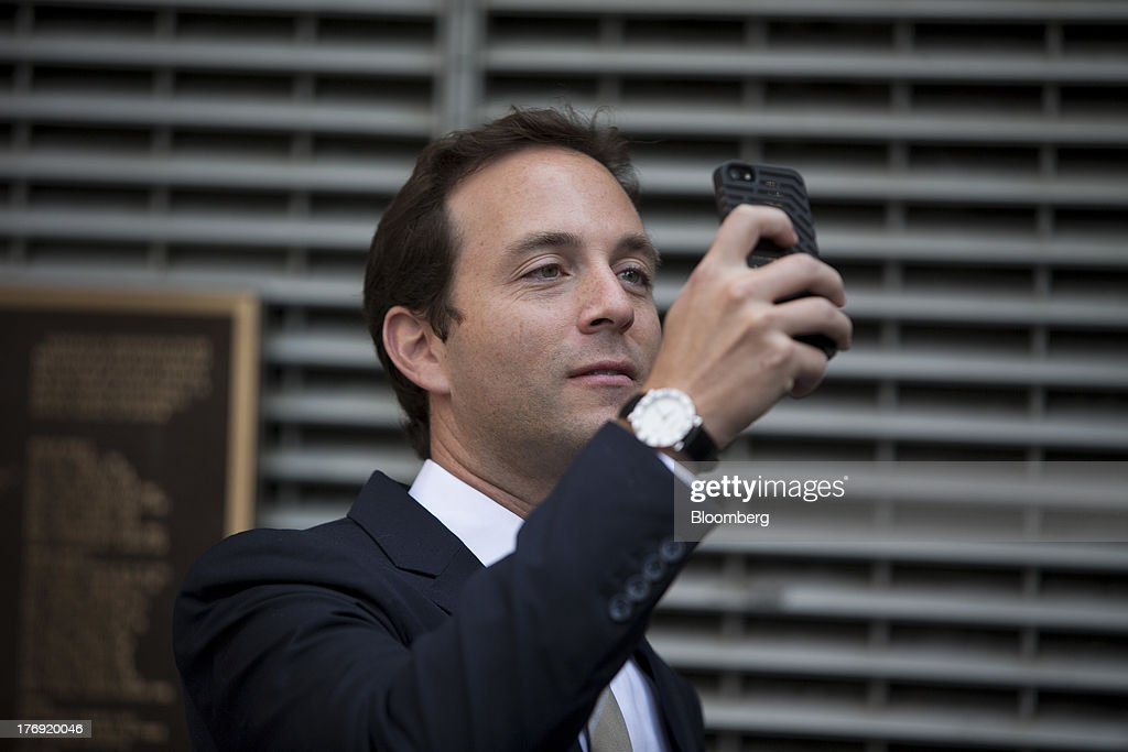 Spencer Rascoff, chief executive officer of Zillow Inc., takes a photograph on his mobile phone in front of the Nasdaq MarketSite in New York, U.S., on Monday, Aug. 19, 2013. Zillow Inc., operator of the largest U.S. real-estate website, agreed to acquire StreetEasy for $50 million in cash to expand its coverage of the New York market. Photographer: Scott Eells/Bloomberg via Getty Images