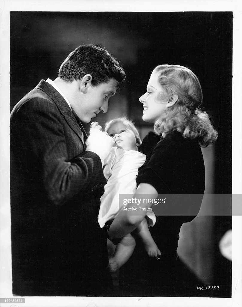 Spencer Tracy and Jean Harlow hold a baby in a scene from the film 'Riffraff', 1936.