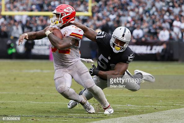 Spencer Ware of the Kansas City Chiefs breaks a tackle by Bruce Irvin of the Oakland Raiders during their NFL game at OaklandAlameda County Coliseum...