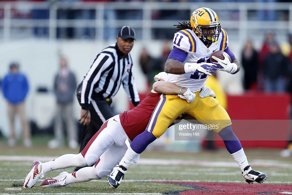 Spencer Ware #11 of the LSU Tigers is tackled from behind during a game against the Arkansas Razorbacks at Razorback Stadium on November 23, 2012 in Fayetteville, Arkansas. The Tigers defeated the Razorbacks 20-13.