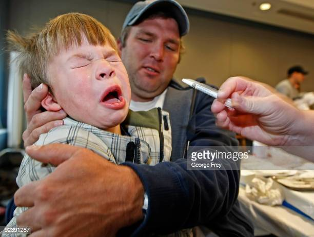 Spencer Whatcott pulls away after a nurse gives an nasal spray of the H1N1 vaccine while his father Cameron hold him at the Utah County Health...