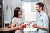 Two cheerful young people holding coffee cups and talking while standing in office