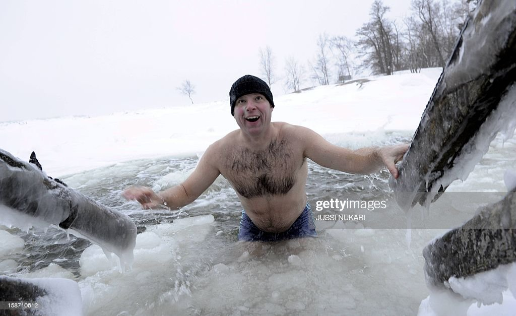 Spending christmas in Finland, Kai Kubierske from Bonn in Germany gets out after swimming in a hole made in the ice at the Gulf of Finland on December 25, 2012 in Lauttasaari, Helsinki.