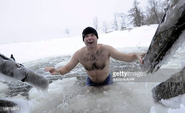 Spending christmas in Finland Kai Kubierske from Bonn in Germany gets out after swimming in a hole made in the ice at the Gulf of Finland on December...