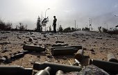 Spent bullet shells litter the ground as a member of the Islamistlinked militia of Misrata walks past following three days of battles in the area of...