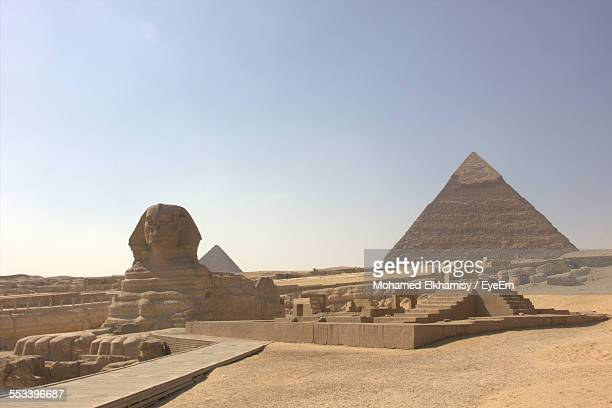 Sphinx With Pyramids In Background