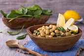 Spiced chickpeas with spinach in a wooden bowl and on wooden table