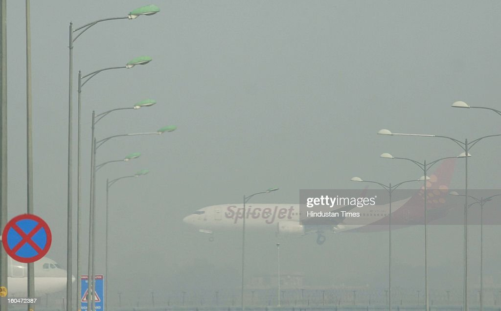 A Spicejet passengers aircraft seen landing at the Indira Gandhi Airport amid dense fog on February 1, 2013 in New Delhi, India. Dense fog badly affected visibility, which dropped to less than 50 m and led to the cancellation of 10 trains and delaying over 130 flights, diversions and cancellations of 19 each.