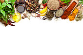 Top view of a large group of multi colored spices and herbs arranged in a row at the top border making a frame and leaving useful copy space for text and/or logo on white background. Spices and herb i
