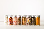 Spices Set in Mini Bottles, such as basil, turmeric, salts, chilli flakes, cumin seeds on light background