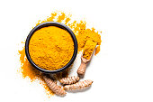 Spices: Top view of a black bowl filled with turmeric powder isolated on white background. A wooden serving scoop with turmeric powder is beside the bowl and turmeric powder is scattered on the table.