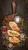 Spicy baked chicken breast on rustic wooden gutting board, top view