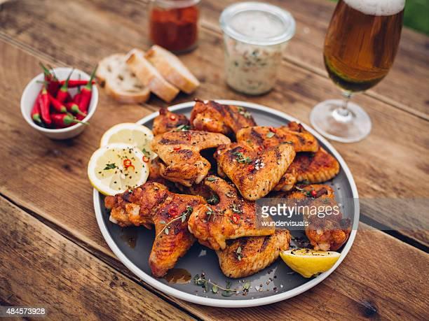 Würzige chicken wings mit Beilagen und einem Glas Bier