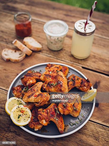 Spicy chicken wings with summer beverage and condiments
